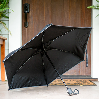 "TUMI<sup>&reg;</sup> Small Umbrella - With the push of a button you can open and close this small, portable umbrella. 35"" canopy with reflective edging and sure-grip carry handle, rubber wrist strap and storage sleeve make this comfortable to use and easy to stow."